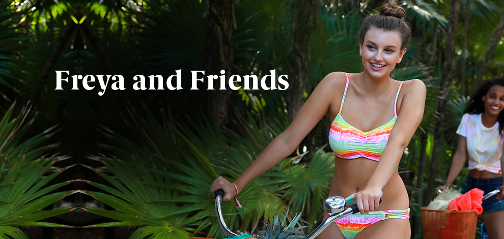 A thin white woman in a Freya bikini rides a bicycle past tropical palm trees, followed by a thin black woman on another bicycle wearing a t-shirt and shorts.