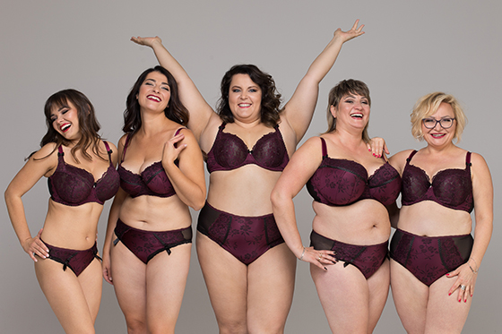 Five white women ranging in size from very thin to medium fat stand against a gray background. They're each wearing matching purple bra and panty sets and look relaxed and happy.