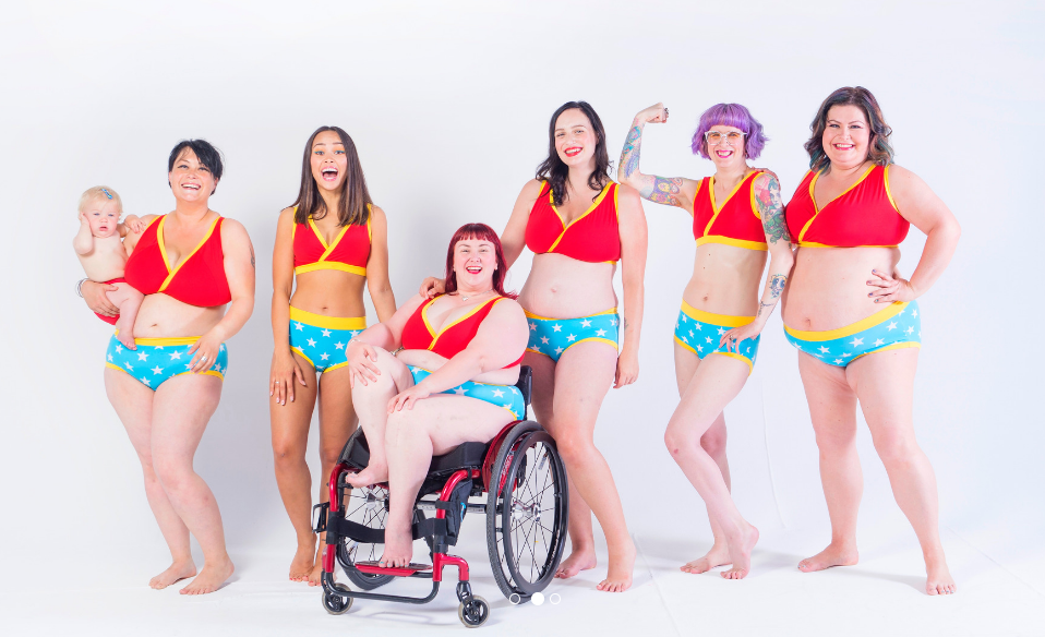 Six women and a baby are shown on a white background. All are white and have a variety of body sizes, and one is using a wheelchair. They're wearing a Wonder Woman-themed bra and panty set from Molke.