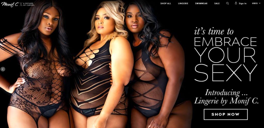 Three women of color stand on a black background. One has blonde hair and two have black hair. All three are wearing strappy, translucent black bodysuits with cutouts. Text next to them reads, It's time to embrace your sexy. Introducing Lingerie by Monif C.