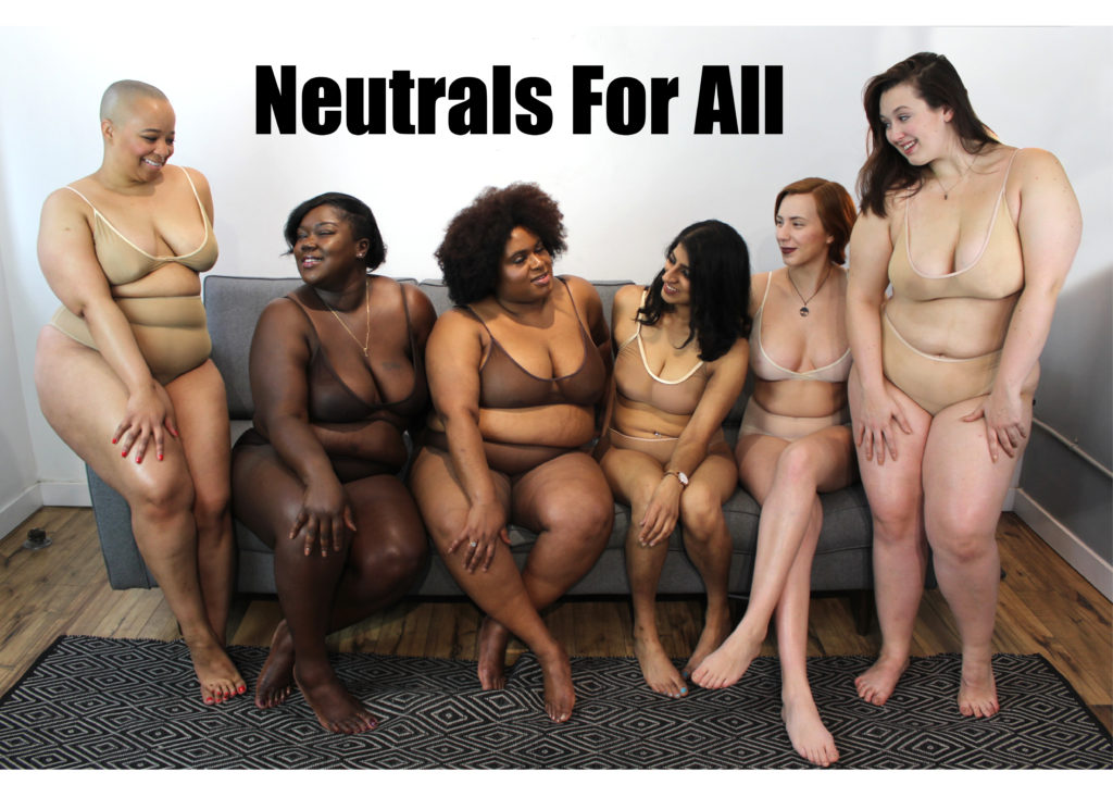 Plus size lingerie company SmartGlamour. The image shows six women sitting on a couch, with skin tones from very pale to dark brown. Each one is wearing a bra and panty set in material that approximates their skin tone. They all look happy and relaxed.