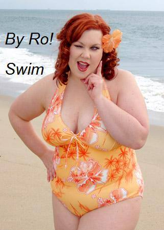 Infinite Swim: Where to Find Swimsuits in Sizes 32+  Swimwear for superfats, infinifats and over size 32 with By Ro! Designs. A woman with pale skin and red hair is standing on a beach. She's wearing an orange one-piece bathing suit and an orange flower in her hair, and is winking with one hand at her face in a flirty pose.