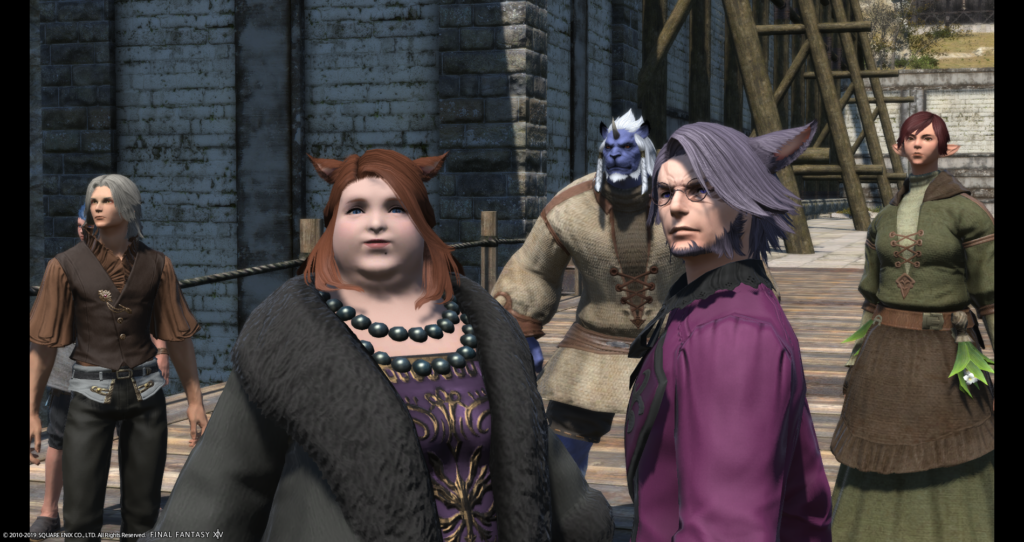 A character from the MMO Final Fantasy XIV, Dulia-Chai, is shown standing in front of a stone wall outdoors. She is fat and pale-skinned, has red hair and cat ears, and is wearing court clothing of a purple and gold full-length dress, black pearls, and black fur coat. A man in a purple coat with purple hair and cat ears stands next to her, with three other fantasy characters in the background.