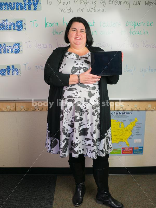 Education Stock Photo: Plus Size Elementary School Teacher Holding Tablet - Body Liberation Photos