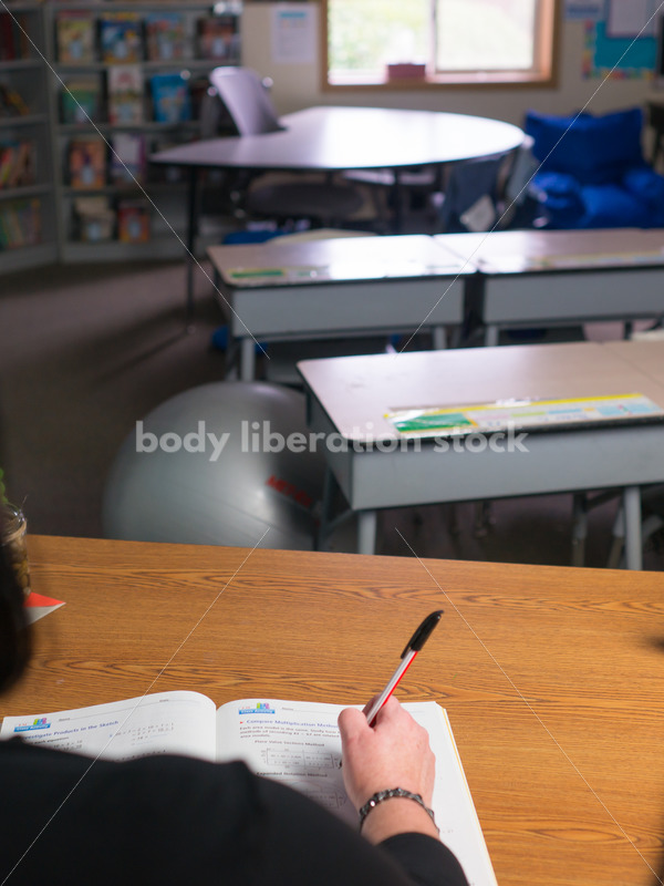 Education Stock Photo: Plus Size Teacher Grading Papers - Body Liberation Photos