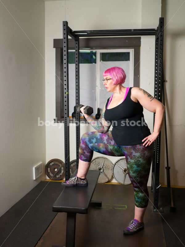 HAES Stock Photo: Female Weightlifter with Pink Hair Lifts Hand Weights in Gym - Body Liberation Photos
