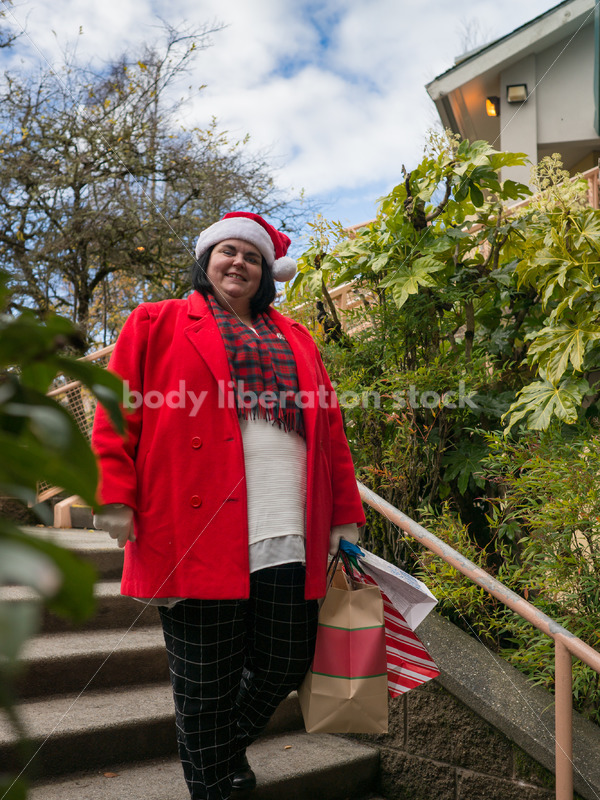 Holiday Stock Photo: Plus Size Woman in Santa Hat with Gift Bags - Body Liberation Photos