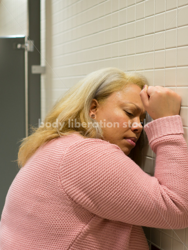Mental Health and Illness Stock Image: Depressed Plus Size Woman in Office Building Bathroom - Body Liberation Photos