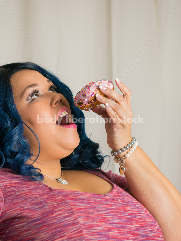 Royalty Free Stock Photo: African American Woman Eats a Doughnut, World Continues to Turn - Body Liberation Photos
