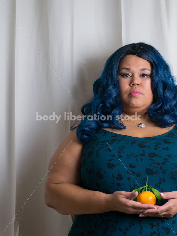 Royalty Free Stock Photo: Black Woman with Satsuma Orange - Body Liberation Photos