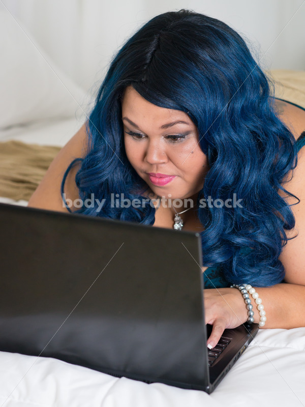 Royalty Free Stock Photo: Plus Size African American Woman Uses Laptop Computer on Bed - Body Liberation Photos