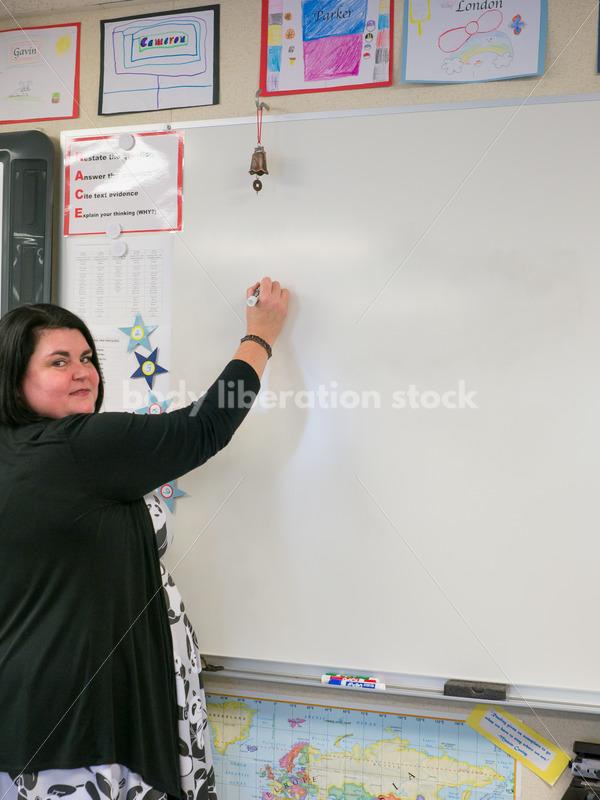 Royalty Free Stock Photo: Plus Size Teacher Writing on Whiteboard - Body Liberation Photos