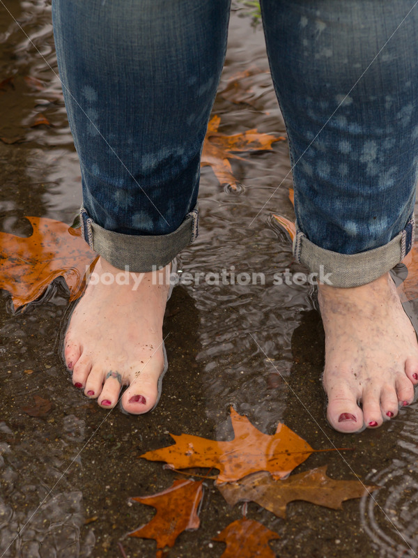 Royalty Free Stock Photo: Plus Size Woman Barefoot in Rain Puddle - Body Liberation Photos