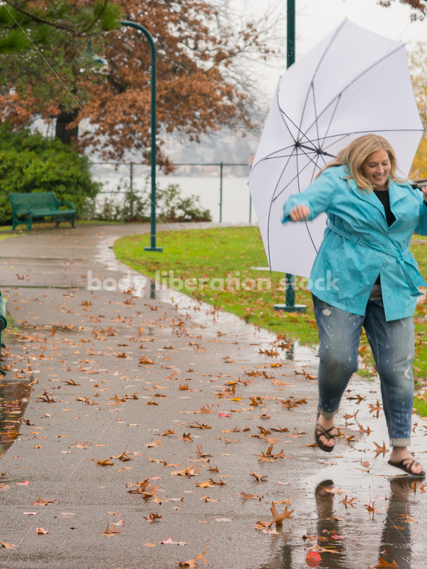 Royalty Free Stock Photo: Plus Size Woman Jumps in Puddle on a Rainy Day in the Park - Body Liberation Photos