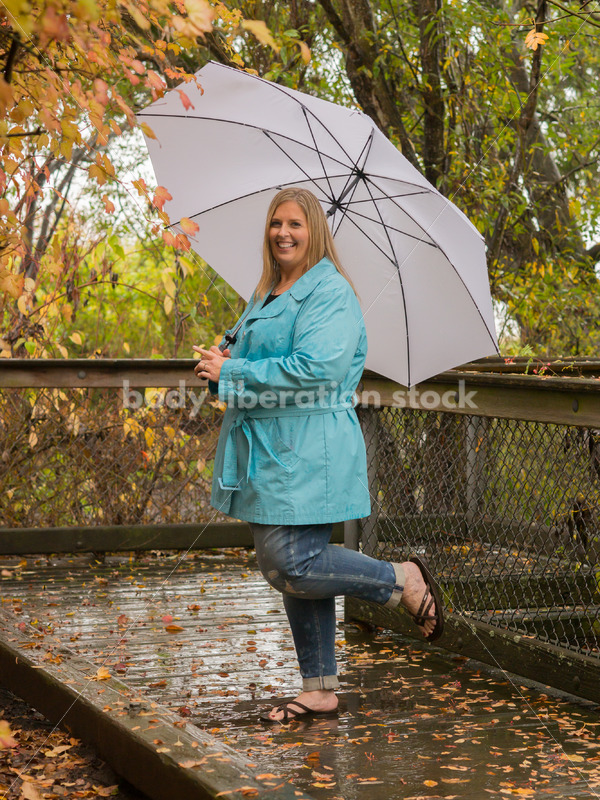 Royalty Free Stock Photo: Plus Size Woman Outdoors with Umbrella, Rain and Autumn Leaves - Body Liberation Photos