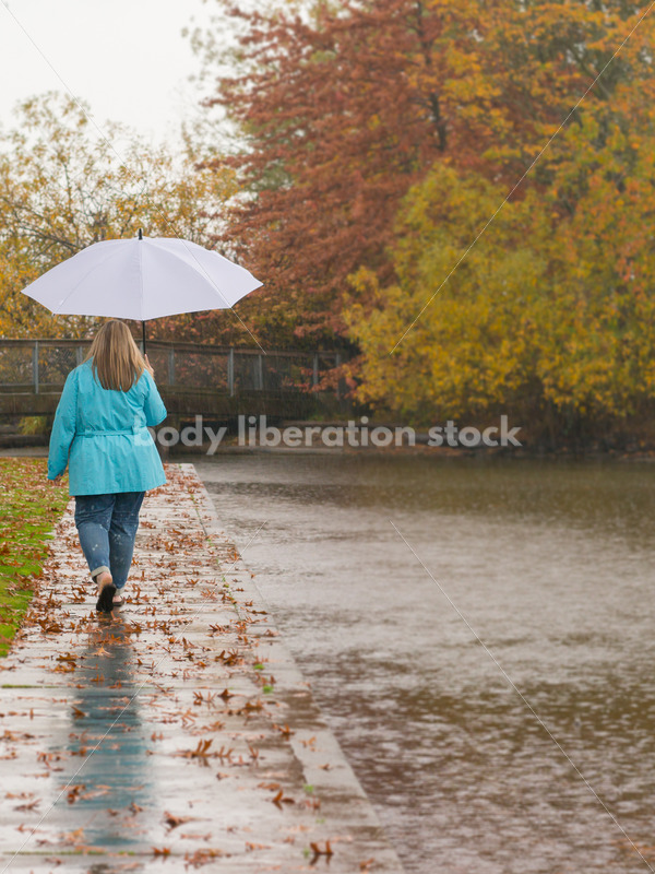 Royalty Free Stock Photo: Plus Size Woman Walks Outdoors by Lake - Body Liberation Photos