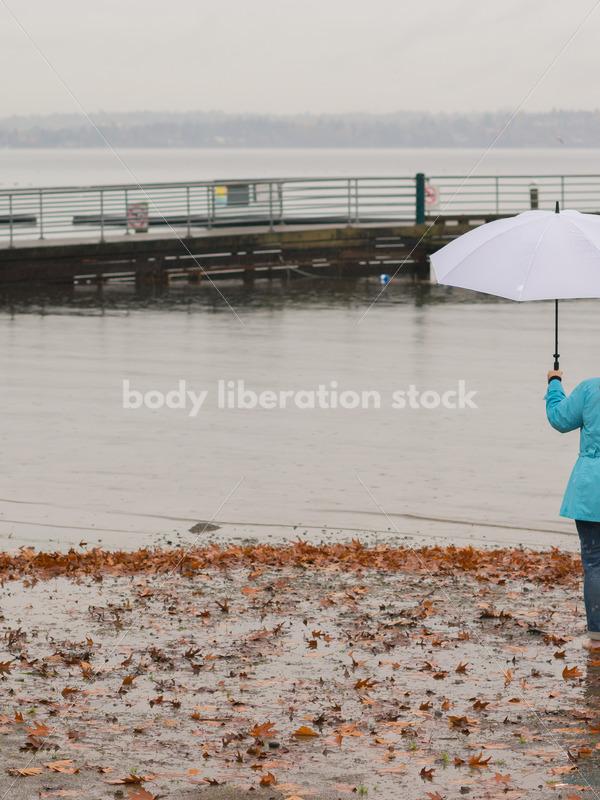 Royalty Free Stock Photo: Plus Size Woman on Lake Shore with Umbrella, Rain and Autumn Leaves - Body Liberation Photos