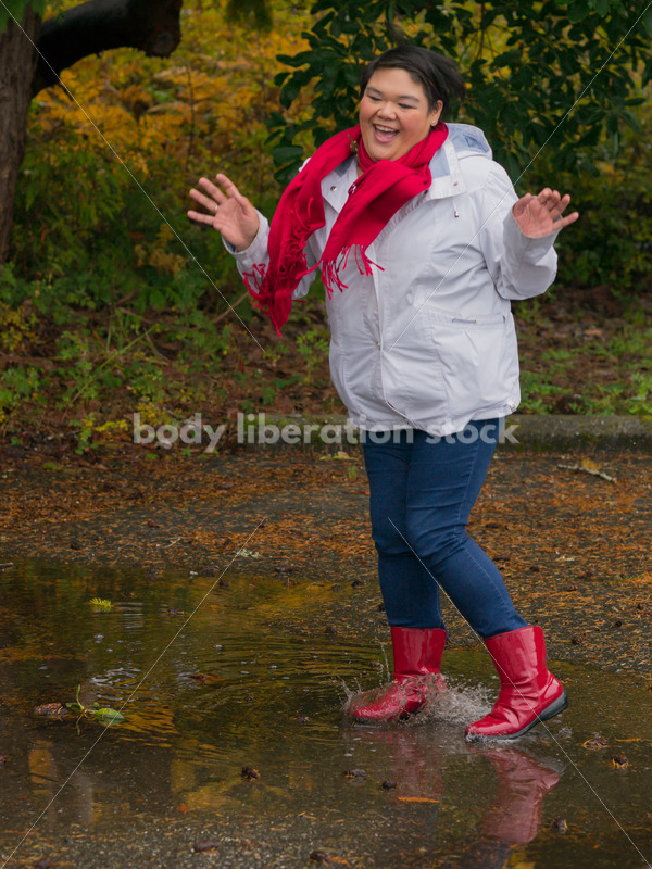Stock Photo: Asian American Woman Playing in Puddles on a Rainy Day - Body Liberation Photos