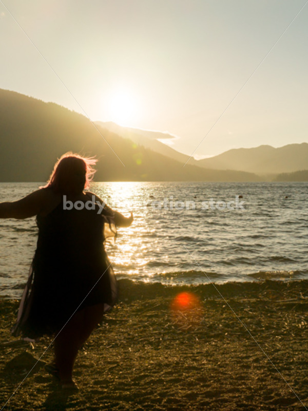 Stock Photo: Plus Size Woman Twirling Sihouette on Mountain Lake Shore at Sunset - Body Liberation Photos