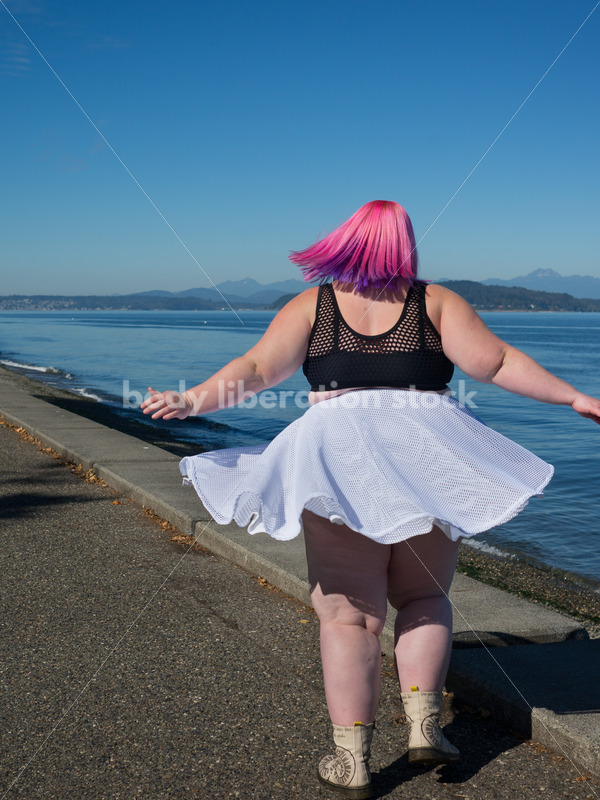 Stock Photo: Plus Size Woman with Pink Hair Twirls near Water - Body Liberation Photos