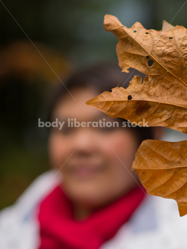 Stock Photo: Young Asian American Woman Holding Autumn Leaf - Body Liberation Photos