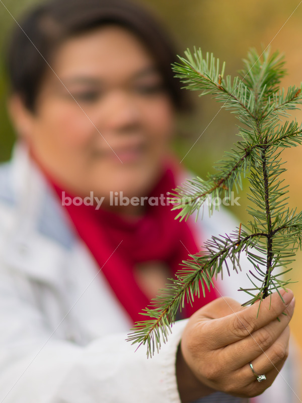 Stock Photo: Young Asian American Woman Holding Pine Branch - Body Liberation Photos