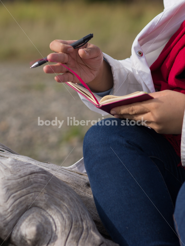 Stock Photo: Young Asian American Woman Writing in Journal Outdoors - Body Liberation Photos