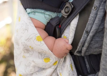 Image description: A fat white baby's arm is partially seen between an overlapping floral blanket, blue onesie sleeve and the body and strap of a car's seat and child safety seat. Image source: Al Soot on Unsplash