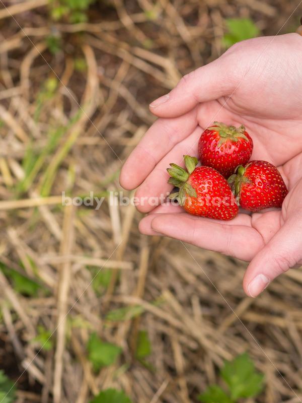 Diverse Gardening Stock Photo: Agender Person Picks Strawberries - Body Liberation Photos