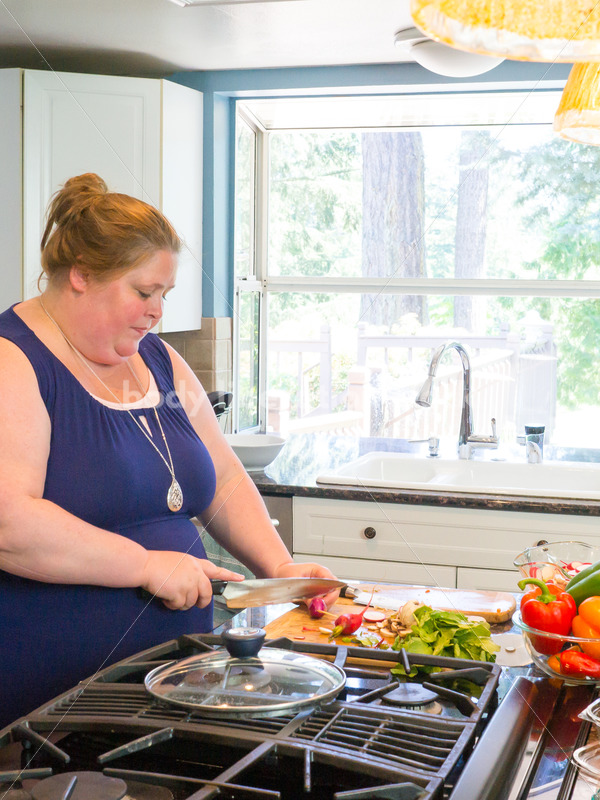 Eating Disorder Recovery Stock Photo: Woman Chopping Peppers on Kitchen Counter - Body Liberation Photos