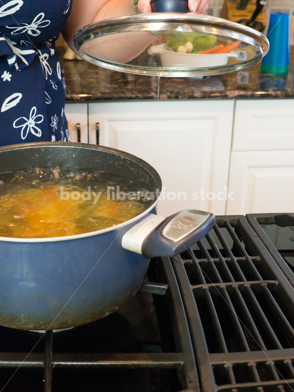 Eating Disorder Recovery Stock Photo: Woman Cooks Pasta in Pot of Water in Kitchen - Body Liberation Photos
