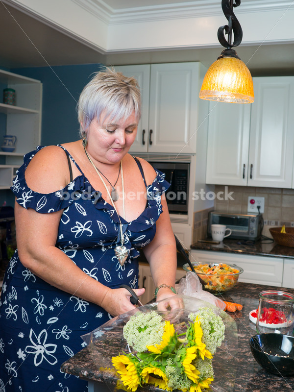 Eating Disorder Recovery Stock Photo: Woman Cuts Flowers in Kitchen - Body Liberation Photos