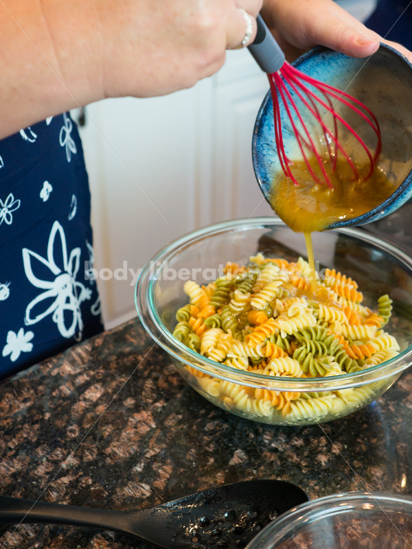 Eating Disorder Recovery Stock Photo: Woman Makes Pasta Salad in Kitchen - Body Liberation Photos