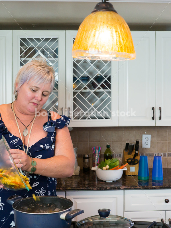 Eating Disorder Recovery Stock Photo: Woman Pouring Pasta into Pot of Water in Kitchen - Body Liberation Photos