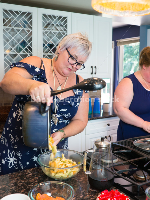 Eating Disorder Recovery Stock Photo: Woman Pours Pasta in Kitchen - Body Liberation Photos