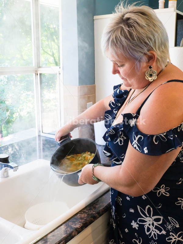 Eating Disorder Recovery Stock Photo: Woman Strains Pasta in Pot of Water in Kitchen - Body Liberation Photos