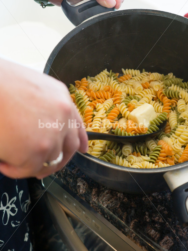 Intuitive Eating Recovery Stock Photo: Woman Adds Butter to Pasta in Kitchen - Body Liberation Photos