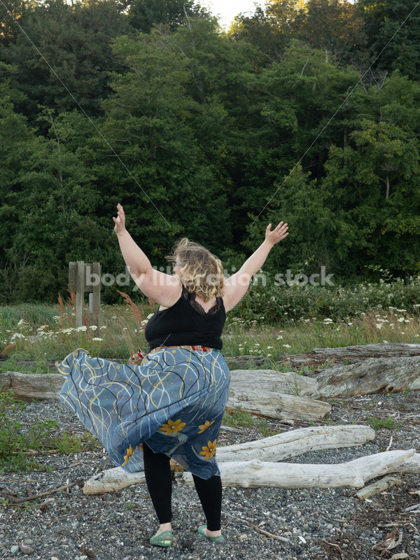 Joyful Movement Stock Image: Plus-Size Woman Twirls on Pebbled Beach at Dusk - Body Liberation Photos