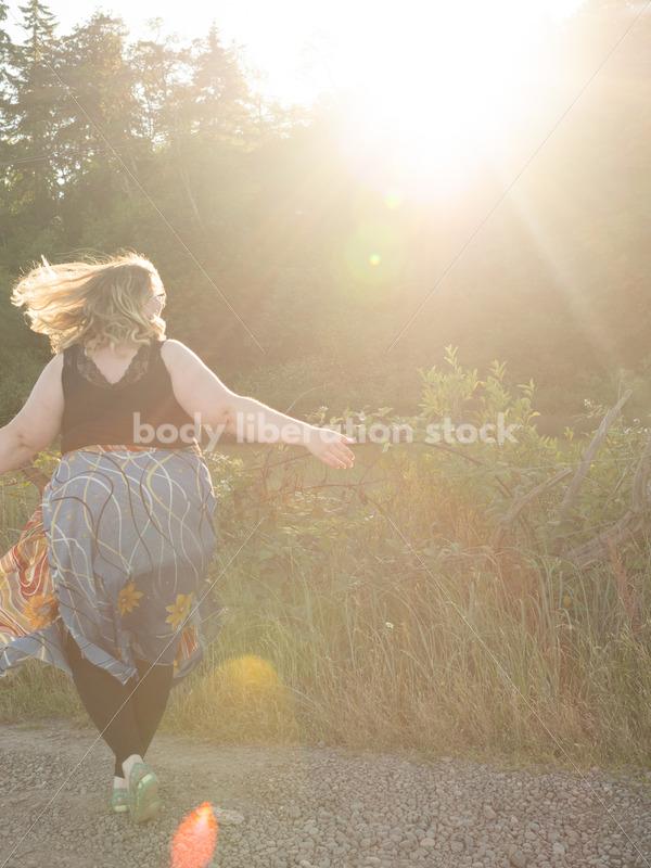 Joyful Movement Stock Image: Plus-Size Woman Twirls on Rural Road at Golden Hour - Body Liberation Photos