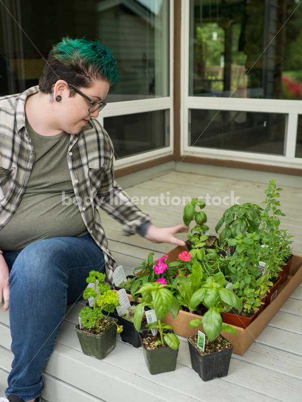 Stock Photo: Agender Person Chooses Plants while Gardening - Body Liberation Photos