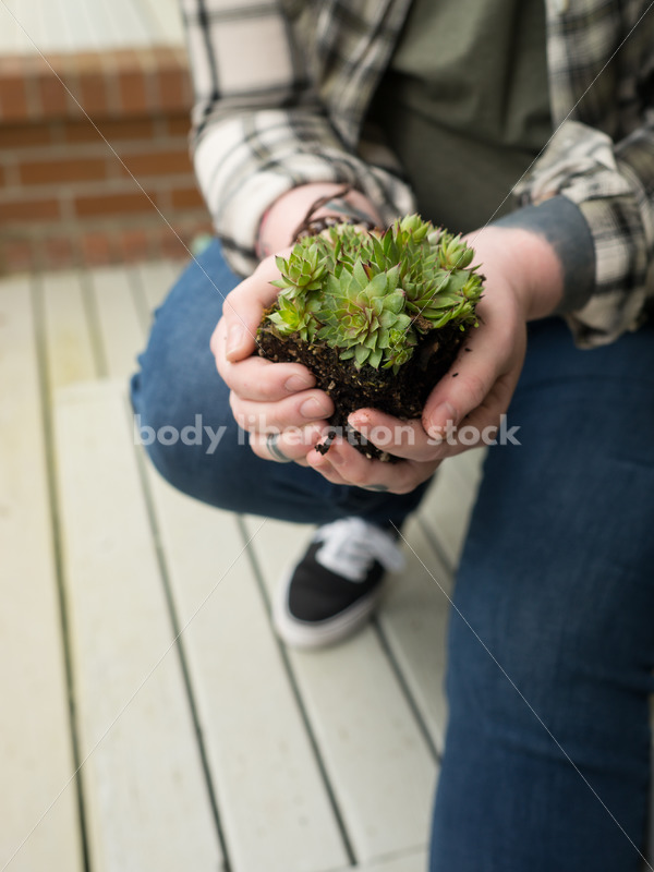 Stock Photo: Agender Person Holding Plant while Gardening - Body Liberation Photos