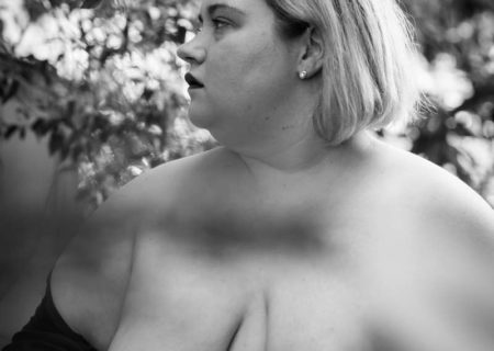 Image description: A fat white women with shoulder-length blonde hair is shown in a black and white image with a black drape just covering the tips of her breasts and part of her torso. She is looking off to one side with a solemn expression, with tree limbs behind her.