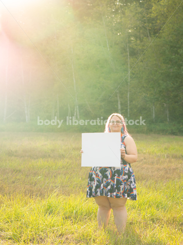 Blank Sign Stock Image: Woman in Field with Sign, Ready for Copy - Body Liberation Photos