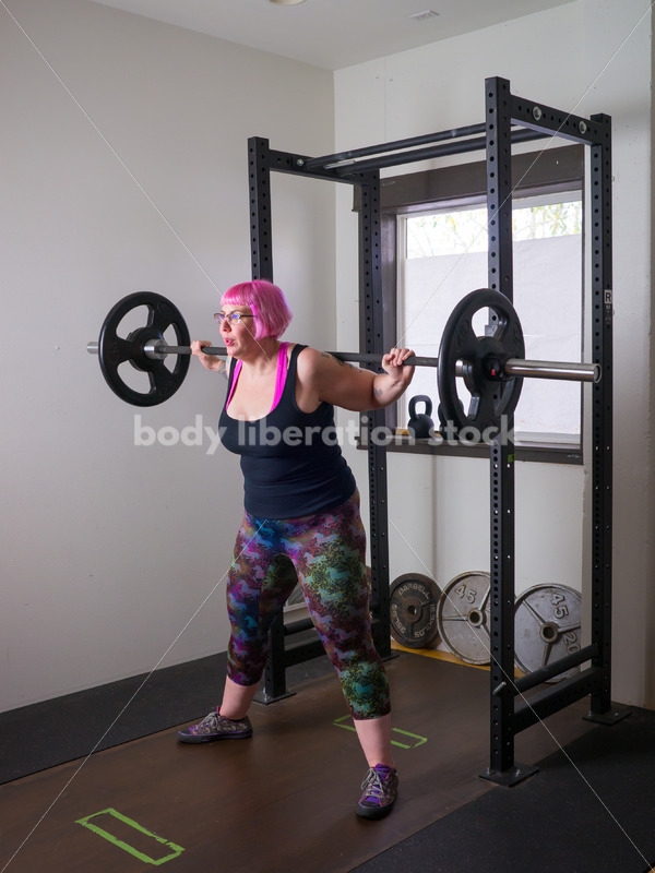 HAES Stock Photo: Female Weightlifter with Pink Hair Does Squat in Gym - Body Liberation Photos
