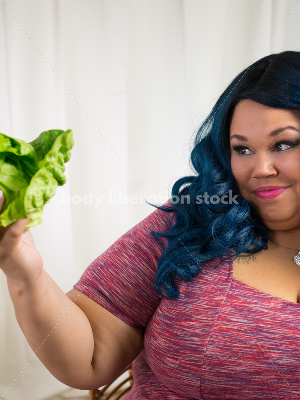 Royalty Free Stock Photo for Intuitive Eating: Black Woman Looks at Head of Lettuce - Body Liberation Photos