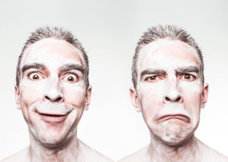 A thin white man with close-cropped hair is shown from the neck up in two shots, side by side. In the first, he has a manic smile. In the second, he has an exaggerated frown. In both shots, his face and neck are covered with a pasty white substance.