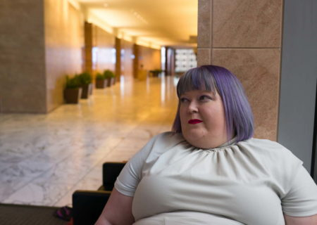 Image description: A fat white woman with purple hair, red lipstick and a gray short-sleeved dress is shown from the bust up. She is sitting in the lobby of a large corporate office building. An empty hallway with marble floors and large plants in planters stretches out behind her. End image description.
