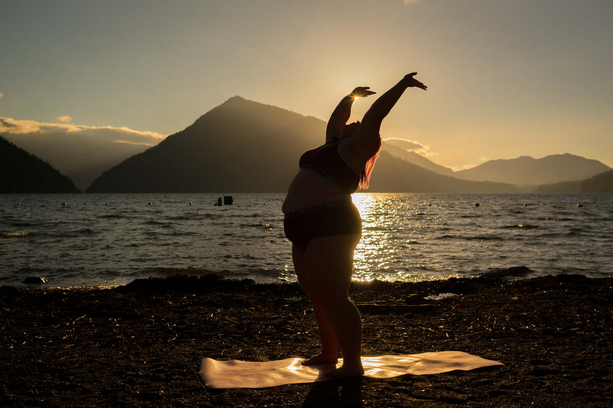 A fat woman with pink hair stands on a yoga mat and throws her arms joyfully into the sky as she begins to move into a yoga pose. A beautiful lake shore, distant mountains and sunset glow complete the image.