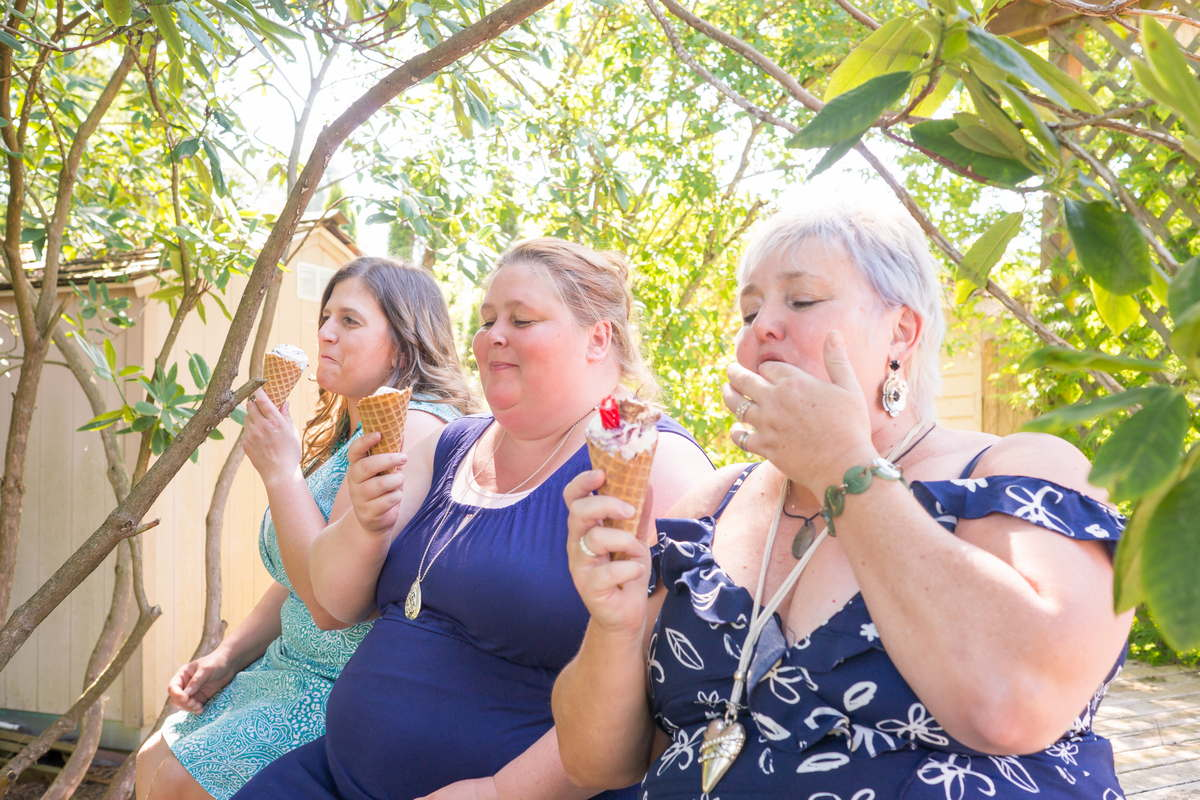 Three fat women sit outside under trees in summer dresses and eat ice cream cones.