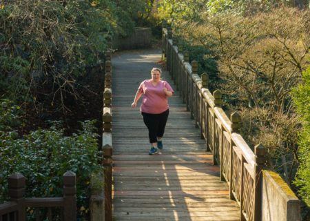 A fat white woman in pink t-shirt and black pants runs towards the camera along a wooden bridge surrounded by a green forest.
